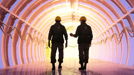 Two mining workers walking in a tunnel