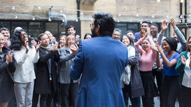 Un orateur devant un groupe de personnes qui applaudissent