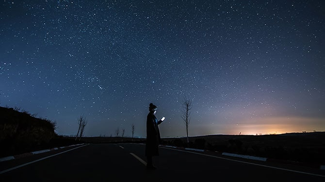 Man holding a phone at night with stars in the background