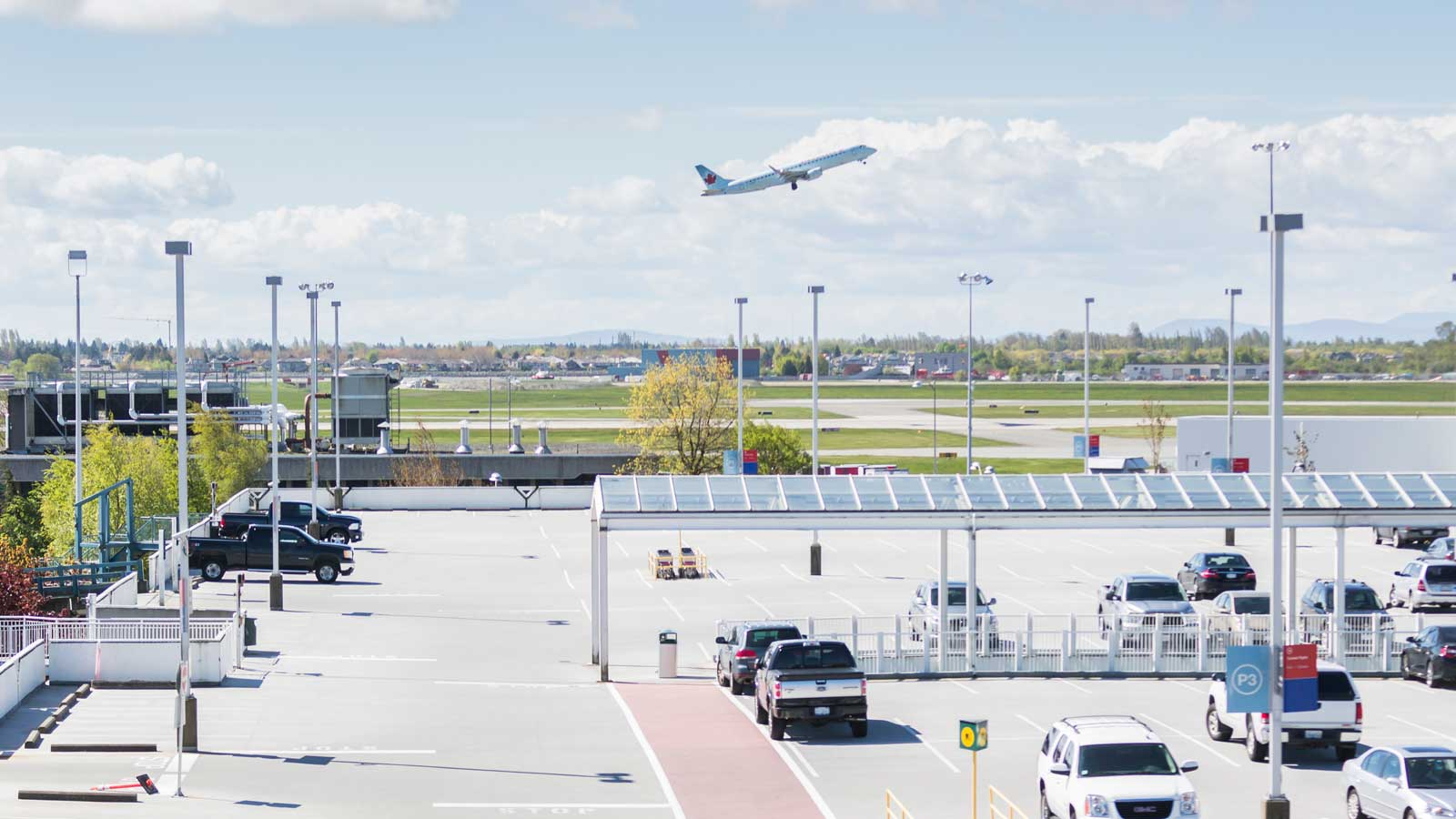 Car park with cars at an airport with plane taking off
